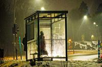 Stockholm, Sweden A person waits at a busstop in the freezing rain.