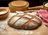 baked loaf of bread on the table and ingredients, kitchen utensils lie nearby, top view.
