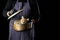 a man chef in a striped blue apron holds an aluminum cauldron in his hand, a cute funny Scottish straight-eared kitten sits inside, black background.