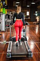 Woman exercising cardio, running workout on treadmill at fitness gym. High quality photo.