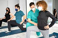 Group of persons on yoga mats assisted by physiotherapist at the rehabilitation clinic. High quality photo.