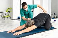 Therapist with protective face mask Assisting patient With Stretching Exercises. High quality photo.