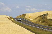 Car driving on a rural highway in the Palouse farming area of eastern Washington State, USA.