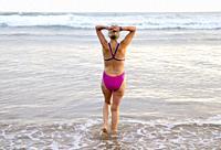 Europe, Spain, Gipuzkoa, Zarautz Beach with older woman bathing at dawn.