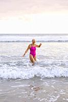 Europe, Spain, Gipuzkoa, Zarautz Beach with attractive older woman bathing at dawn.