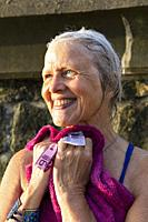 Europe, Spain, Gipuzkoa, Zarautz Beach with attractive older woman showering after her swim.