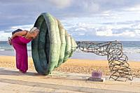 Europe, Spain, Gipuzkoa, Zarautz Beach with Sculpture shaped like a horn being investigated by a woman tourist.