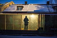 Stockholm, Sweden A man and his shadow stands on the Karrtorp subway or tunnelbana platform in the morning winter sun.