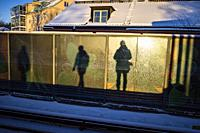 Stockholm, Sweden Pedestrians and their shadows stand on the Karrtorp subway or tunnelbana platform in the morning winter sun.