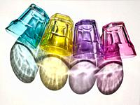 Four colored crystal glasses and their shadows on white background.