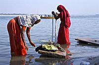 hindu women washing saris and other fabrics on ghats in benares, up, india.
