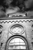 Rose window on the facade of an old brick building.