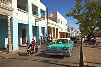 Cyclist and cars in front of the colonial buildings at Paseo Del Prado or so-called Boulevard, Cienfuegos, Cienfuegos Province, Cuba, West Indies, Cen...