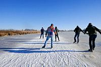 ice skaters at Giethoorn lake in Holland