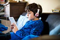 boy listens to music from tablet sitting in house-boy watches video on smartphone with headphones.
