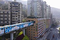 Aerial view of subway train at Liziba station in Chongqing, China, passing through building.