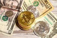 Close-up of Bitcoin cryptocurrency and United States currency.
