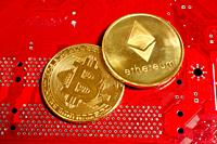 Close-up of Bitcoin and Ethereum cryptocurrency with a red motherboard background.