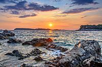 Sunset over rocky beach.