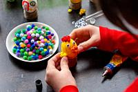 A girl glues wings to a chicken figurine made from an egg.