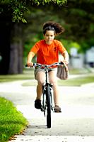Girl riding bicycle on a warm summer day.