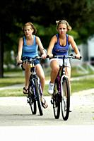 Two 2 girls riding bicycles on a warm sunny day.