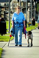Blind woman walks her dog on a warm sunny day.