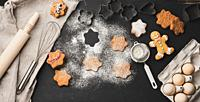 Star shaped baked gingerbread cookies sprinkled with powdered sugar on a black table, top view.