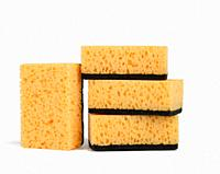 stack of yellow kitchen sponges isolated on white background, close up.