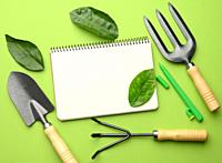 open notebook with blank white sheets and various gardening tools with wooden handles on green background, flat lay, copy space.