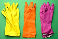 three pairs of rubber gloves for cleaning on a green background, top view.