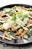 chinese cantonese style steamed spicy fish fillet with vegetables on hot plate.