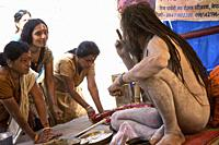 naga baba balakgiri in encampment on the benares gaths, offering blessing and good karma to hindu pilgrims a few days before the shivaratri. benares, ...