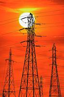 Sun sets over electrical power lines and towers.