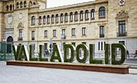 The name of the city of Valladolid written on a poster with plant letters appears in front of the façade of the Academia de Caballería, in the Zorrill...