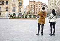 A young man and a young woman take a picture of the name of the city of Valladolid written on a poster with plant letters that appears in front of the...