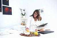 Woman having breakfast in bed and reading a newspaper