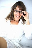 Woman in bed smiling wearing her glasses