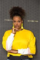 Serious black curly haired millennial female in trendy bright yellow blouse and earrings touching chin and looking at camera against mesh wall.
