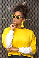 Confident young African American female model in bright yellow blouse and trendy sunglasses and earrings touching chin and looking away.