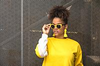Confident young African American fashionable female in bright yellow blouse and earrings adjusting trendy sunglasses while standing against mesh fence...