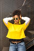 Contemporary millennial black female in stylish yellow sunglasses and earrings with bright blouse and jeans touching hair while standing against mesh ...