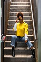 Full body of modern young black female in trendy yellow shirt and sunglasses sitting on staircase and looking at camera.