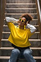 Cheerful young African American female in trendy vivid yellow shirt and sunglasses with earrings having fun and touching head while sitting on stairwa...