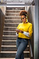 Happy youthful African American female in trendy yellow outfit and sunglasses listening to music through wireless headphones and messaging on smartpho...
