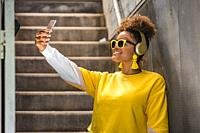 Happy millennial African American female in vivid yellow wear and trendy sunglasses taking selfie on mobile phone while listening to music with headph...