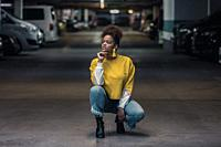 Full body of confident contemplative young African American female in bright yellow shirt and stylish earrings squatting and looking away pensively in...