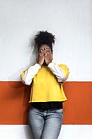 Unrecognizable African American female in bright yellow shirt and jeans covering face with hands while standing against wall.