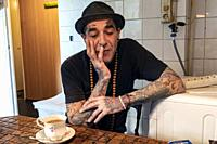 Tilburg, Netherlands. Portrait of a middle aged man with an abundance of tattoos having tea inside his vintage kitchen.
