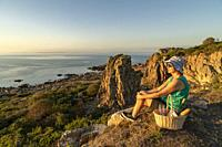 Woman sitting on a cliff in sunset having a picnic basket with wine, glasses and bread, nice warm evening light, Hovs hallar, Skåne, Sweden.
